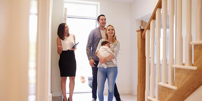 realtor-showing-young-family-around-property-for-sale-picture-id546201672